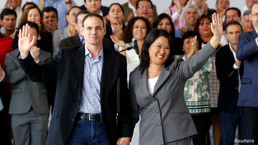 Peruvian presidential candidate Keiko Fujimori, accompanied by her husband Mark Villanella and elected congressmen, waves to the media after Peru's electoral office ONPE said she lost against Pedro Pablo Kuczynski in the country's presidential electi