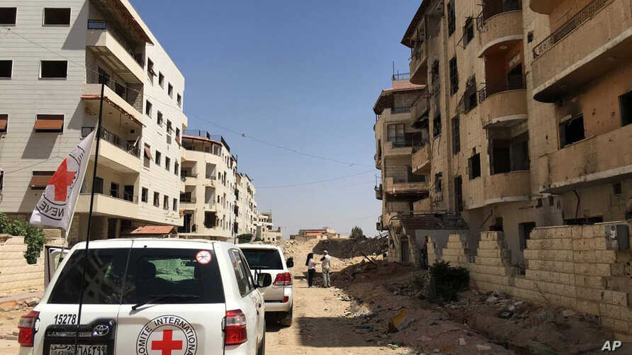 FILE - A June 1, 2016 photo released by the International Committee for the Red Cross shows the first humanitarian aid convoy in Daraya, Syria.