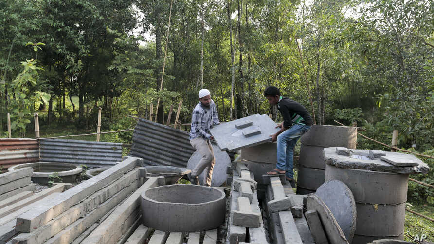 FILE - In this May 30, 2016 photo, Bangladeshi volunteers, working to spread awareness on sanitation, lift toilet seats in Bormi village, near Dhaka, Bangladesh.