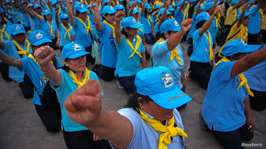 King's volunteers wearing blue caps and yellow foulards shout slogans before the start of the cleaning program at a market in Bangkok, Aug. 8, 2018.