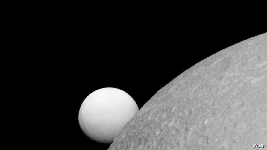 Dione with Enceladus in the background. This image was taken by the Cassini spacecraft on 8 September 2015.