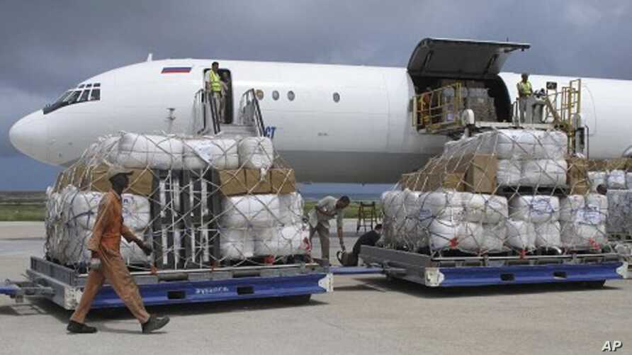 Tons of relief from the United Nations High Commissioner for Refugees (UNHCR) are offloaded after landing at Mogadishu airport, Somalia, Monday, Aug. 8, 2011