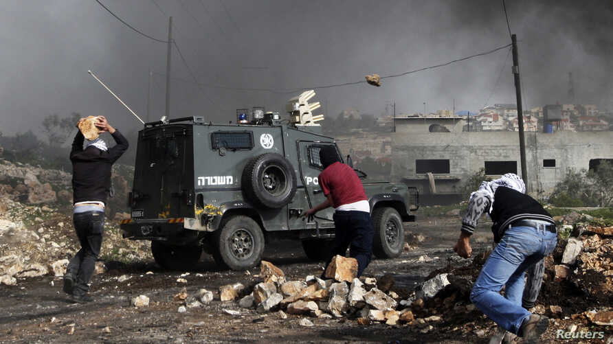 Palestinian protesters throw rocks at an Israeli border police vehicle during clashes at a weekly protest against the nearby Jewish settlement of Kdumim, in the West Bank village of Kfar Kadum, near Nablus January 25, 2013.