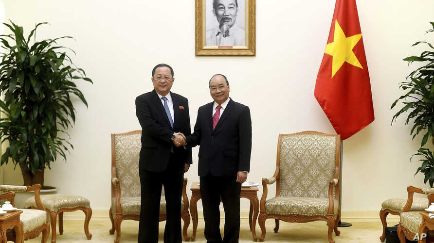 North Korean Foreign Minister Ri Yong Ho, left, poses with Vietnamese Prime Minister Nguyen Xuan Phuc for a photo during a meeting at the Government Office in Hanoi, Vietnam, Saturday, Dec. 1, 2018.
