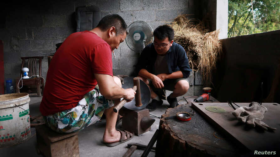 Owner Tian Huan (R) chats with a blacksmith at his workshop for handmade woks in Datian village, Hubei province, China August 13, 2018.