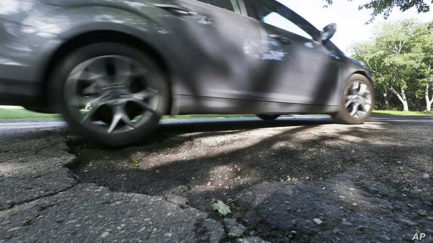 FILE - An automobile drives over a pothole in Bloomfield Township, Michigan.
