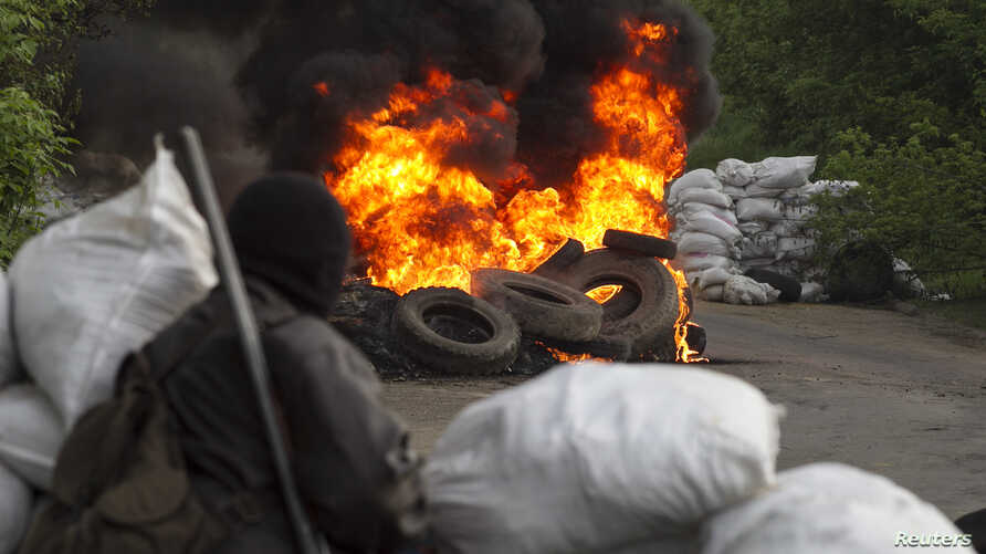 """A pro-Russian separatist guards a checkpoint as tyres burn in front of him, near the town of Slaviansk in eastern Ukraine May 2, 2014. Ukraine launched a """"large-scale operation"""" to retake the eastern town of Slaviansk, pro-Russian separatists there s"""