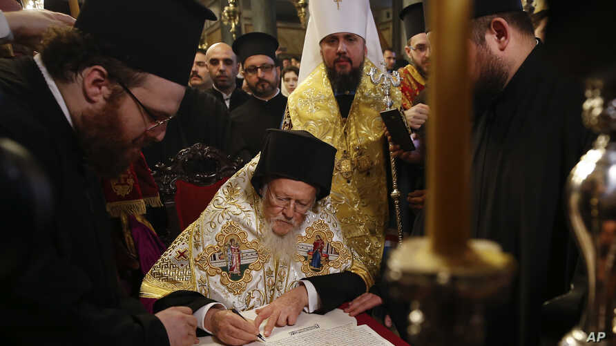 "Ecumenical Patriarch Bartholomew I, center, signs the ""Tomos"" decree of autocephaly for the Ukrainian church as Metropolitan Epiphanius, center right, the head of the independent Ukrainian Orthodox Church looks on during the ceremony at the Patriarch"