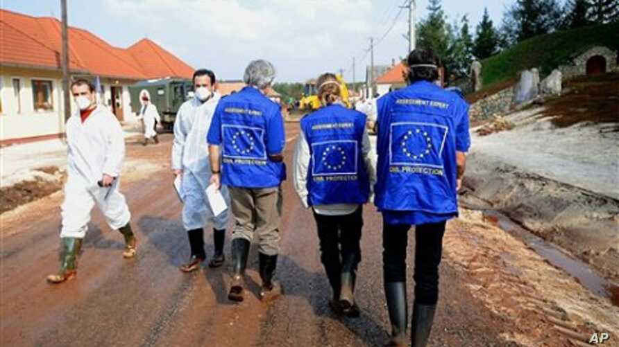 European Union Assessment Experts who are assessing damage caused by toxic red mud flood walk down main street of Kolontar village,164 kms southwest of Budapest, Hungary, 13 Oct. 2010