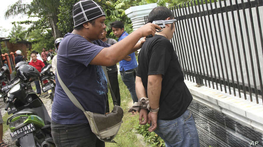 A plain-clothed police officer arrests an inmate who escaped from Sialang Bungkuk Prison in Pekanbaru, Riau province, Indonesia, May 5, 2017. Hundreds of police and soldiers were deployed to search for some scores of inmates who escaped Friday from t