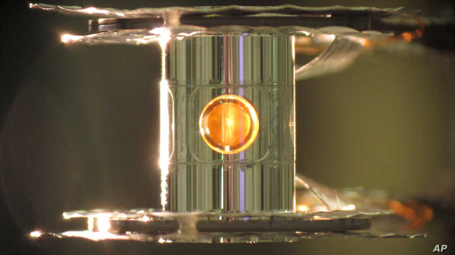 FILE - This undated image provided by the Lawrence Livermore National Laboratory shows a deuterium and tritium capsule, sphere in window at center, inside a cylindrical hohlraum container about 0.4 inches tall, which are used in the controlled fusion