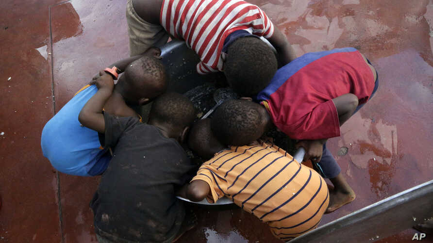 Kids scrape for remaining rice inside a pot at a displacement center in Beira, Mozambique, March 22, 2019.