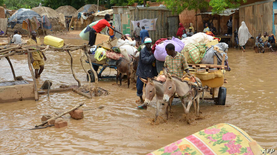 Local residents carry their belongings as they evacuate their homes in Niamey, the capital of Niger, on August 19, 2012.