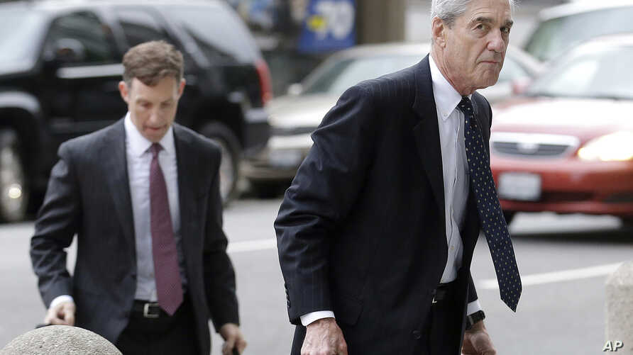 FILE - In this April 21, 2016 file photo, attorney and former FBI Director Robert Mueller, right, arrives for a court hearing at the Phillip Burton Federal Building in San Francisco.