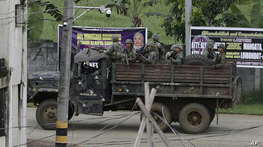 Philippine troopers go around town as fighting continues in Marawi city, southern Philippines, June 9, 2017.