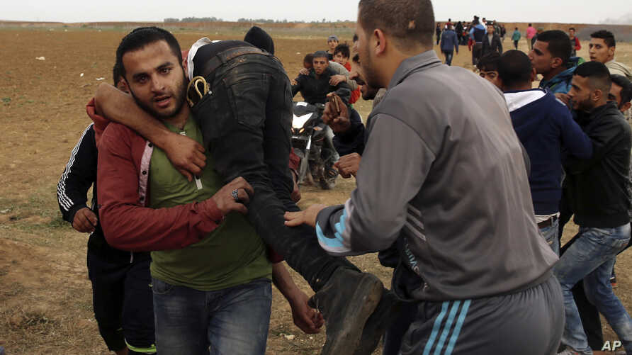 Palestinian protesters evacuate a wounded youth during clashes with Israeli troops along Gaza's border with Israel, east of Beit Lahiya, Gaza Strip, April 3, 2018.
