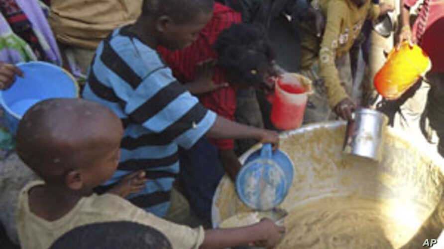 Children from southern Somalia get cooked food at a local NGO's compound in Mogadishu, Somalia, September 14, 2011.