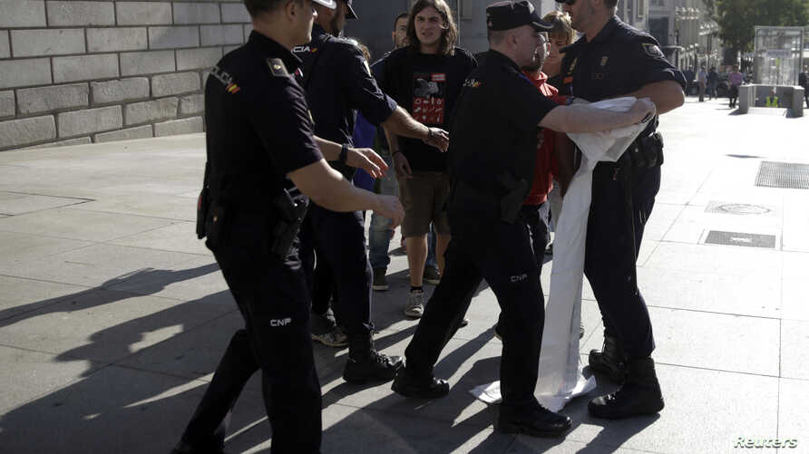 Spanish riot police try to take away a banner from pro-independence supporters during a protest near Spanish parliament in Madrid, Sept. 30, 2014.