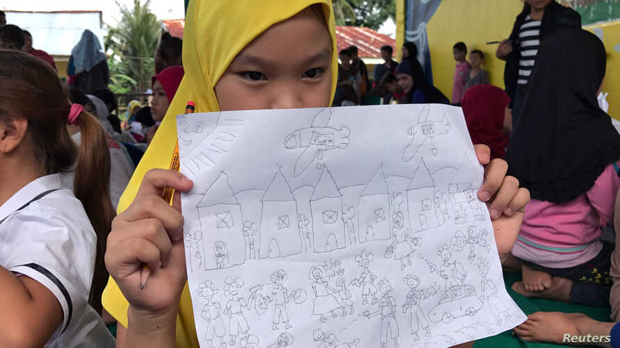 An evacuated student shows her drawing about what she and other Marawi residents experienced before fleeing the city still under siege during a school day at Pantar elementary school in Lanao Del Norte, Philippines, June 6, 2017.