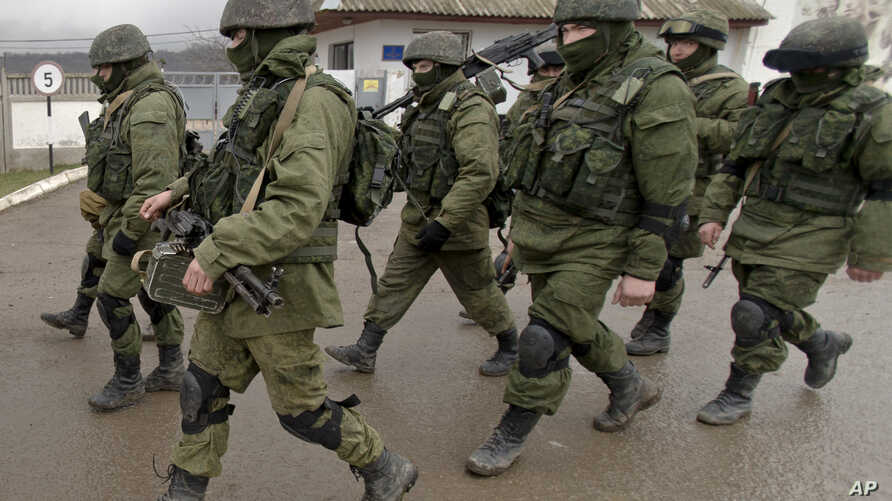 FILE - In this March 20, 2014 photo, Pro-Russian soldiers march outside an Ukrainian military base in Perevalne, Crimea.