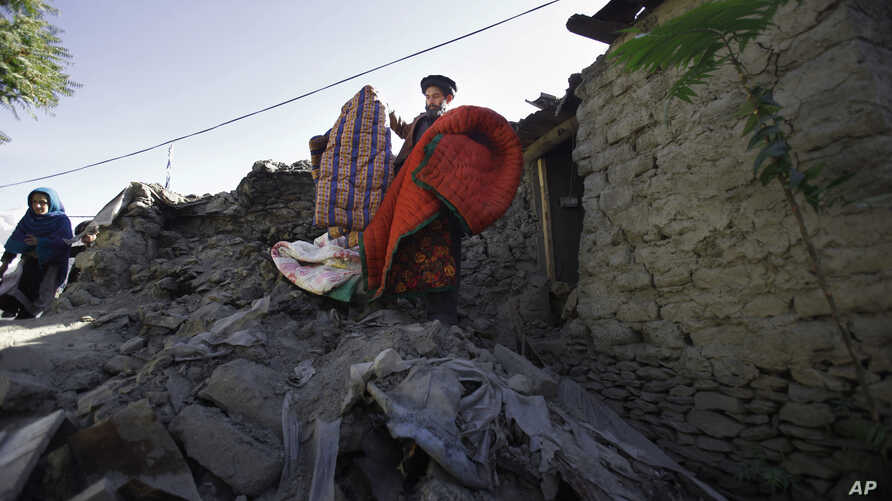 Rehmatud Din, center, who lost his daughter in Monday's earthquake, salvages what he can from his destroyed house caused by Monday's earthquake in Chitral town, northern Pakistan, October 29, 2015.