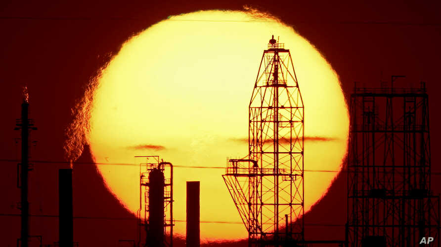 The National Cooperative Refinery Association oil refinery is silhouetted against the setting sun, Aug. 19, 2015, in McPherson, Kan.