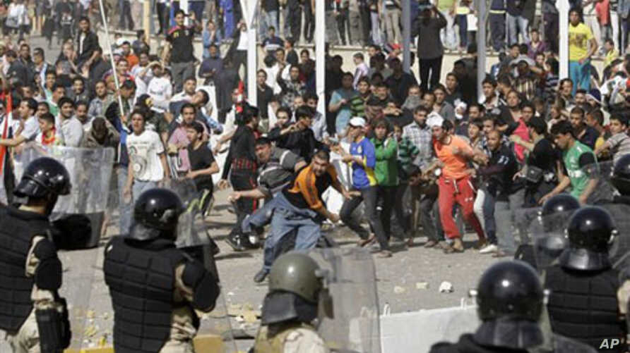Iraqi riot police officers prevent anti-government protesters from entering the heavily guarded Green Zone during a demonstration in Baghdad, February 25, 2011