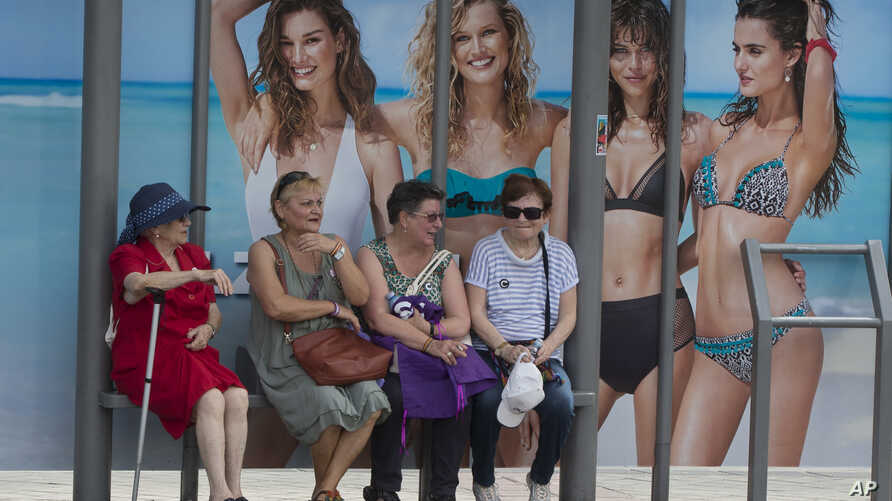 Four women wait at a bus stop in front of an advertising poster for swimwear and beach wear in Madrid, Spain, May 27, 2017. The head of the U.N. for Women is urging advertisers to eliminate such stereotypes in their ads.