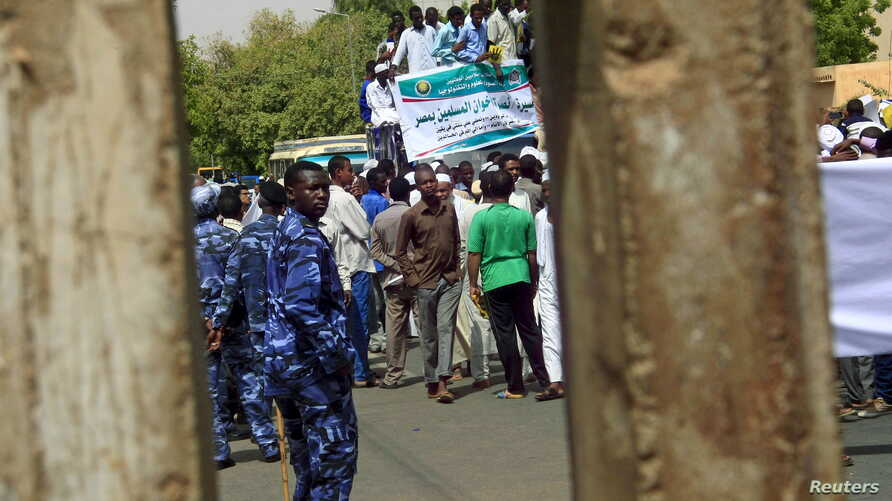 FILE - Policemen (in blue uniforms) keep an eye on protesters during a rally in Khartoum, Sudan, May 22, 2015.
