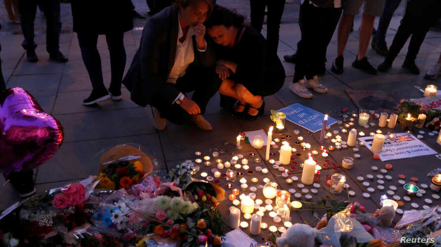 Women pay their respects to all those affected by the bomb attack, following a vigil in central Manchester, Britain, May 23, 2017.