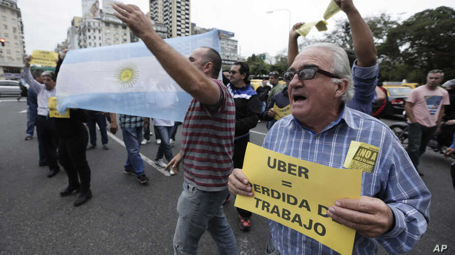 """A taxi driver holds a sign that says in Spanish """"Uber (equals) job loss"""" as he and other cabbies block a main avenue in Buenos Aires, Argentina, April 12, 2016."""