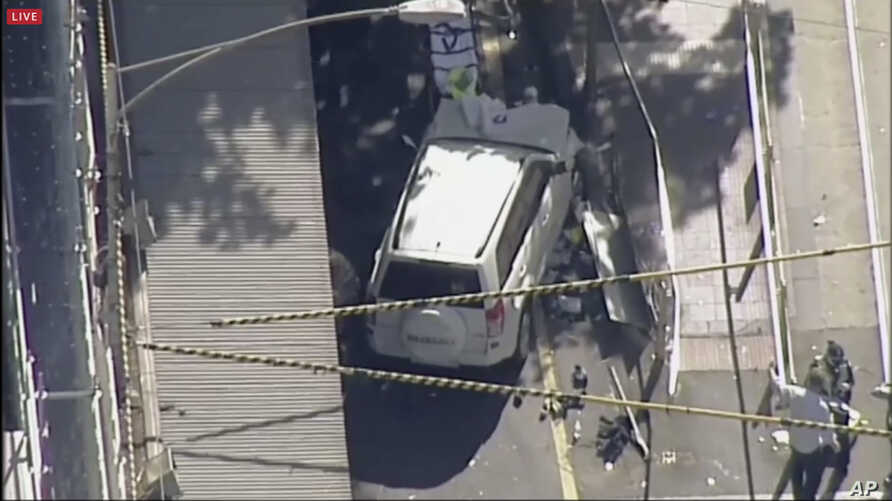 In this photo made video from the Australian Broadcasting Corp., a white SUV vehicle is stopped after allegedly striking pedestrians, Dec. 21, 20217, in Melbourne, Australia. Local media say over a dozen people have been injured after a car drove int...