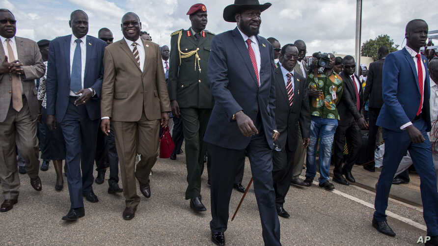 South Sudan's President Salva Kiir, center, arrives back in the country from peace talks in Addis Ababa, at the airport in Juba, South Sudan, June 22, 2018.