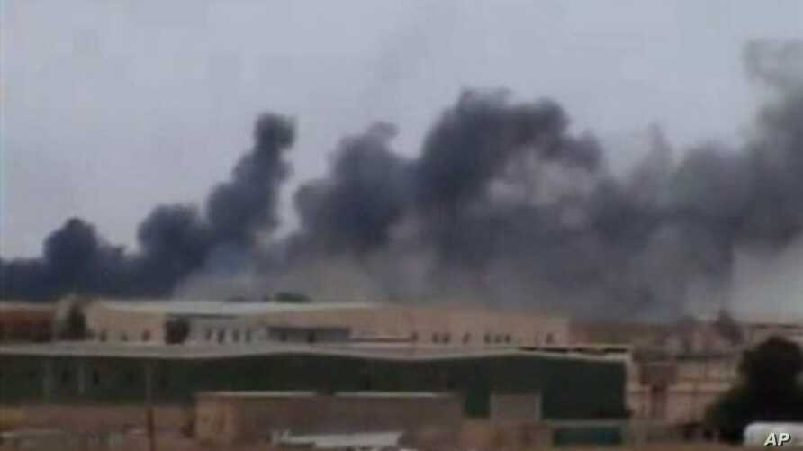 This image taken March 16, 2011 from amateur video and obtained March 17, 2011 shows a plume of smoke rising over the skyline in Ajdabiya, eastern Libya, the last major city between forces loyal to Libyan leader Moammar Gadhafi and rebel-held Benghaz