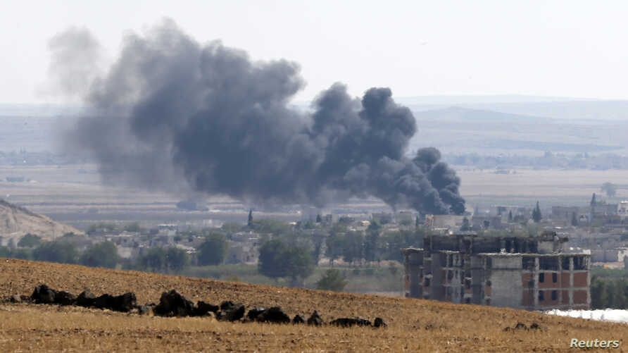 Smoke rises from the Syrian town of Kobani, as seen from near the Mursitpinar border crossing on the Turkish-Syrian border in  Suruc, Oct. 6, 2014.