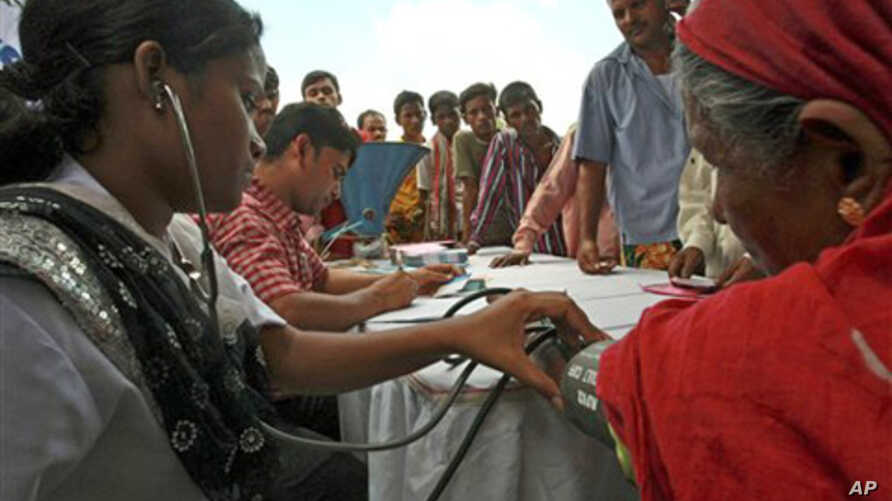 A health worker of a private hospital checks the blood pressure of a slum dweller as others wait at a roadside health camp in Dhaka, Bangladesh, Aug. 5, 2010.