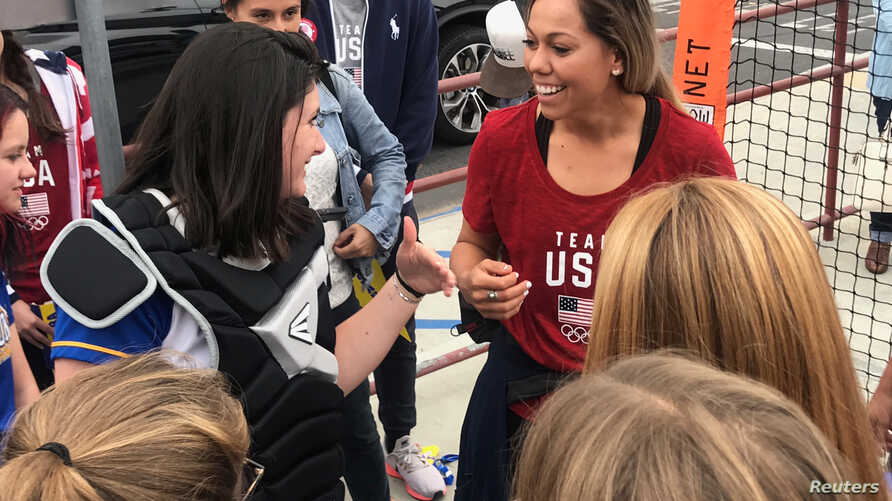Student Hannah August, left, shares a laugh with U.S. National Softball Team catcher Sahvanna Jaquish, during a visit to Agoura High School, in Agoura Hills, California, Dec. 17, 2018.