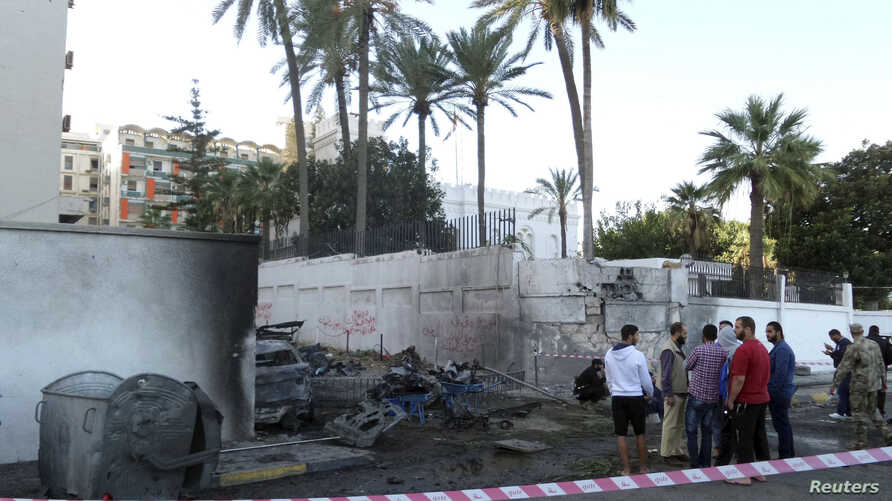 Onlookers and security personnel stand at the scene of a car bomb explosion near the Egyptian embassy in the Libyan capital of Tripoli Nov. 13, 2014.
