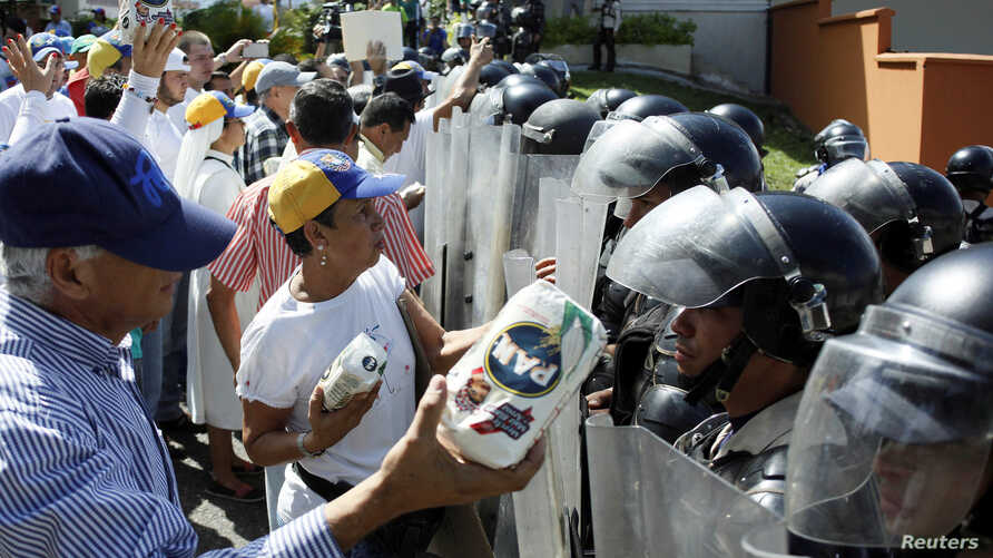 Opposition supporters hold packages of corn flour in front of riot police during a rally against Venezuelan President Nicolas Maduro's government in San Cristobal, Jan. 23, 2017.