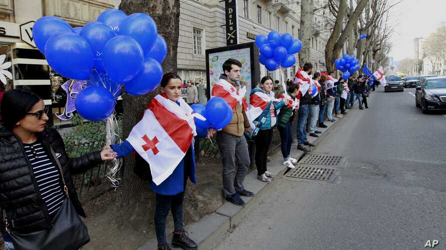 Supporters of the main opposition party wear Georgian national flags during a protest against buying gas from Russia's state-controlled Gazprom, in Tbilisi, Georgia, March 6, 2016.