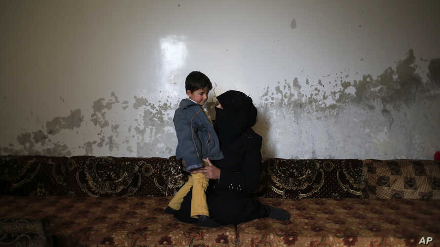 In this Jan. 18, 2017 photo, Elham Saleh, 31, who fled from the village of Deir Hafer, speaks with her son Abdullah, 4, as they sit in a room in the town of Safira, just south of Aleppo, Syria.