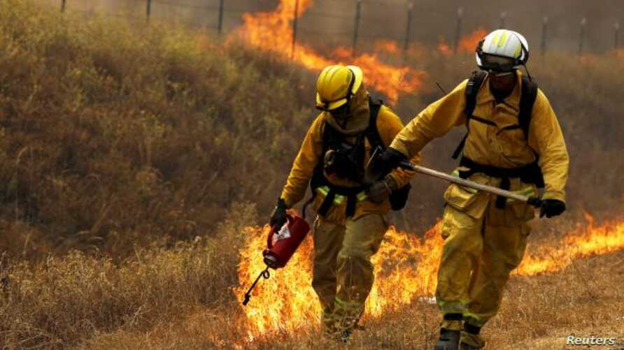 FILE - A California Department of Forestry and Fire Protection (Cal Fire) firefighter sets a backfire with a driptorch along Highway 20 at the Rocky Fire near Lower Lake, California, Aug. 3, 2015.