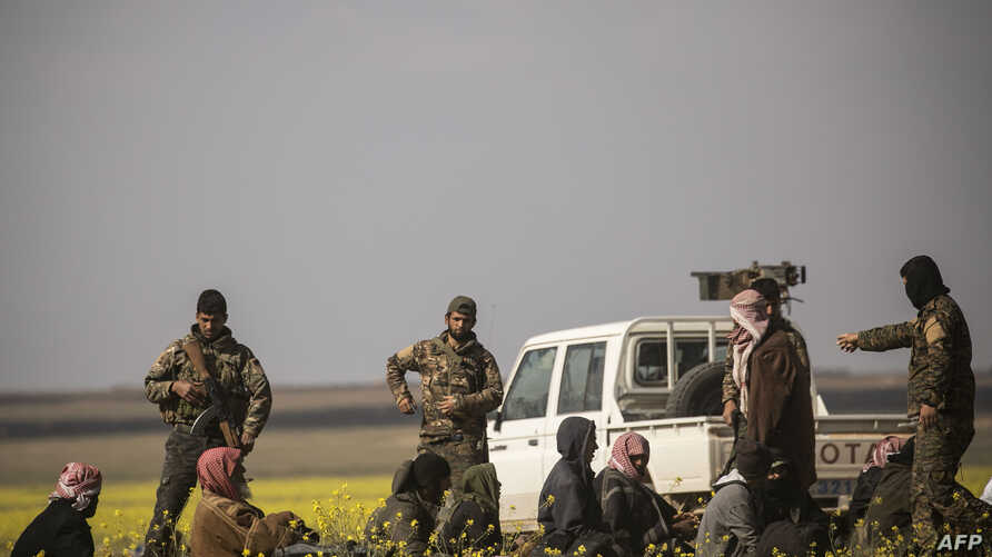 U.S.-backed Syrian Democratic Forces stand guard over men suspected of being Islamic State (IS) group fighters at a screening point outside Baghuz in eastern Syria, March 6, 2019.