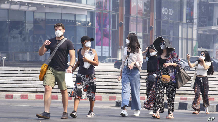 Tourists wear masks in Chiang Mai province, Thailand, Tuesday, April 2, 2019. The air hanging over Thailand's far north has become so polluted, the prime minister went Tuesday to see in person what's been called a severe health crisis.