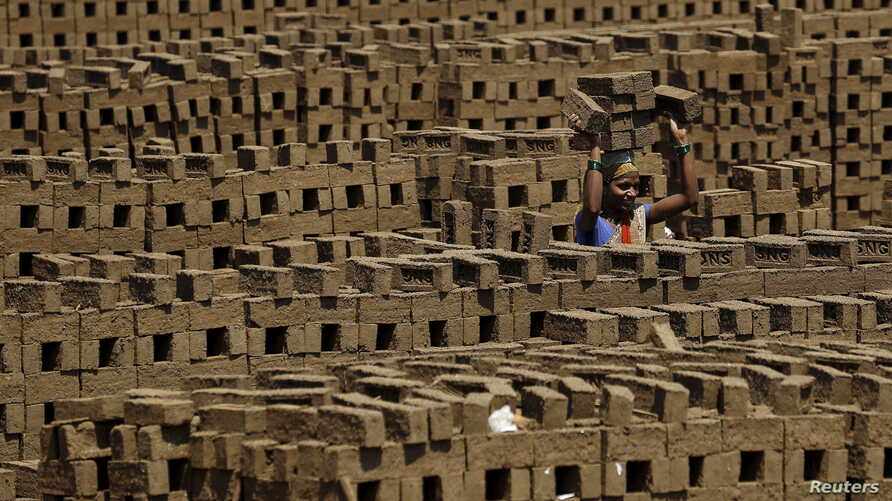 FILE - A laborer carries bricks at a kiln in Karjat, India, March 10, 2016. Thousands of brick kiln workers in India's western Maharashtra state are learning from activists that they have the right to a minimum wage, basic amenities and fair treatmen...