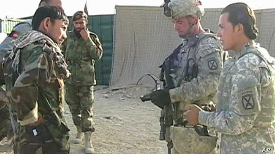 US soldiers (R) talk to Afghan soldiers in training (L)