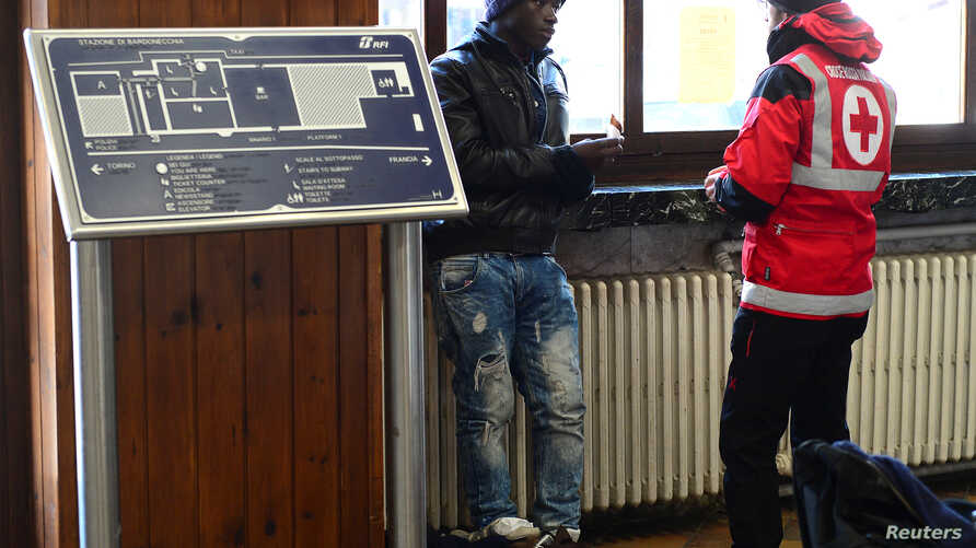 FILE - A Red Cross worker speaks with a migrant at the Bardonecchia railway station, northern Italy, Dec. 28, 2017.