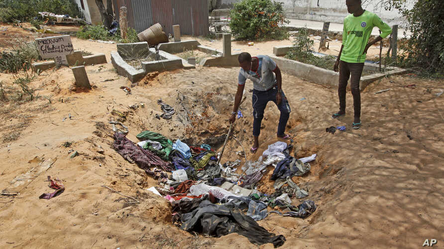 Afrah Ibrahim, center, searches through the clothes of the dead lying in a hole, to try and find the clothes last worn by his missing sister, without success, outside a hospital in Mogadishu, Somalia, Oct. 17, 2017.