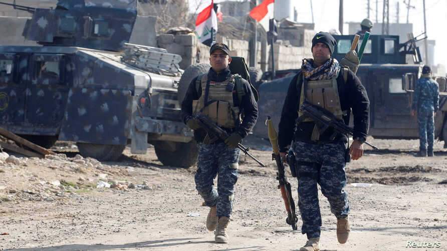 Iraqi security forces carry weapons during a battle with Islamic State militants in the Intisar district of eastern Mosul, Jan. 1, 2017.
