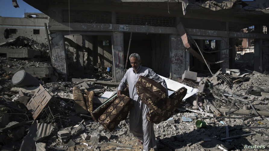 A Palestinian man salvages belongings from damaged buildings in the Shejaia neighborhood, which witnesses said was heavily hit by Israeli shelling and air strikes, in Gaza City July 27, 2014.